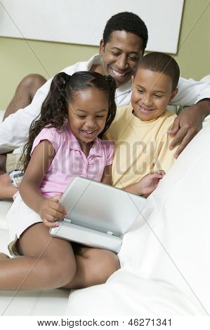 Father with son and daughter watching movie on portable DVD player in the living room