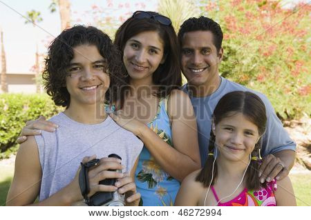 Boy (13-15) holding camcorder standing outdoors with sister (7-9) and parents portrait.