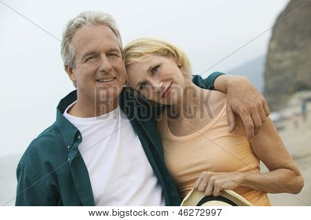 Portrait of a couple man with arm around a woman at the beach