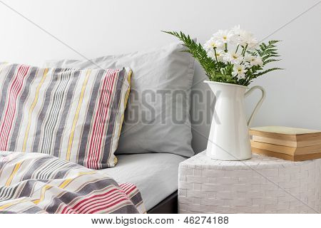 White Flowers And Books On A Bedside Table