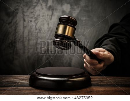 Judge's hold hammer on wooden table
