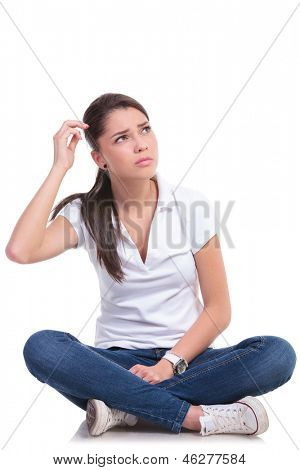 casual young woman sitting with legs crossed and looking up confused. isolated on white background
