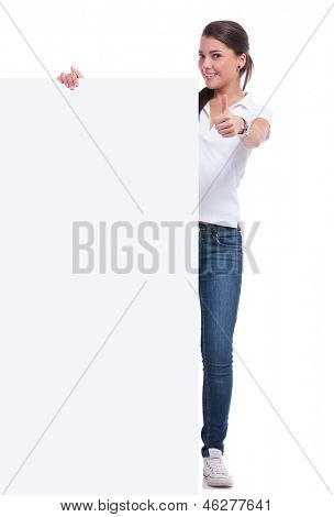 casual young woman presenting an empty pannel and showing the thumbs up sign while smiling to the camera. isolated on white background