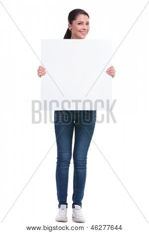 full length picture of a casual young woman holding a blank pannel with voth her hands and smiling to the camera. isolated on white background