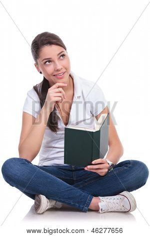 casual young woman sitting with legs crossed and thinking while reading a book, looking up with her hand on her chin. isolated on white background