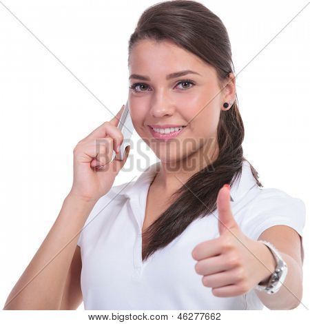 casual young woman showing thumb up sign while on phone. isolated on white background