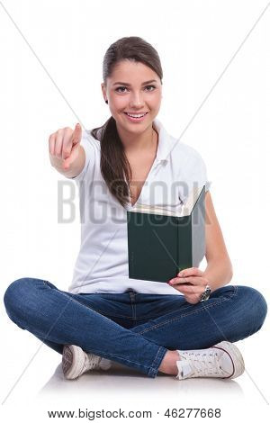 casual young woman sitting with legs crossed and holding a book while pointing and looking at the camera with a smile. isolated on white background