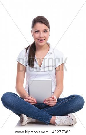 casual young woman sitting with legs crossed and holding a tablet while looking at the camera with a smile. isolated on white background