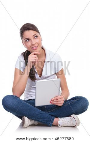 casual young woman sitting with legs crossed and looking up pensively while holding her tablet. isolated on white background