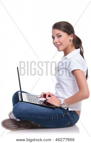side view of a casual young woman sitting with legs crossed and working on her laptop while looking at the camera with a smile. isolated on white background
