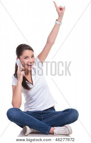 casual young woman sitting with legs crossed and talking on the phone while pointing upwards and looking at the camera with a smile. isolated on white background