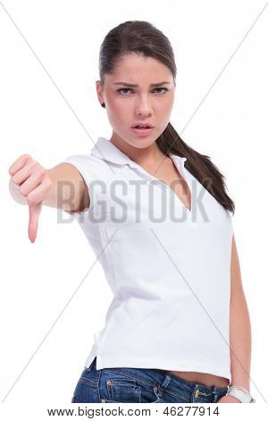 casual young woman showing thumb down gesture while looking at the camera. isolated on white background