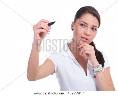 casual young woman writing on an imaginary screen with a marker and holding her hand on her chin. isolated on white background