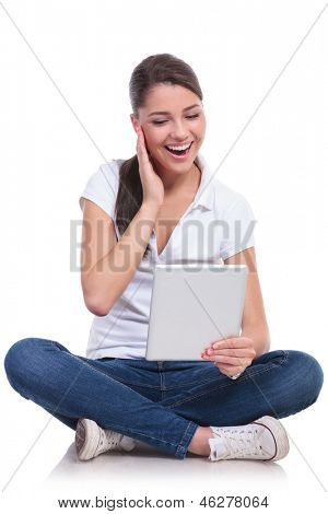 casual young woman sitting with legs crossed and laughing at something she reads on her tablet. isolated on white background