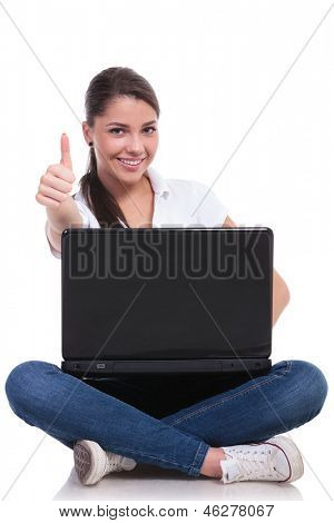 casual young woman sitting with legs crossed and showing thumb up while holding laptop. isolated on white background