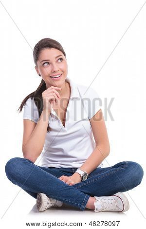 casual young woman sitting with legs crossed having an idea, looking up and holding a hand on her chin. isolated on white background