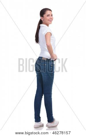 full length picture of a casual young woman standing with her back to the camera and holding a hand on her hip while looking over the shoulder at the camera and smiling. isolated on white background