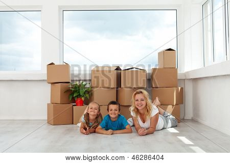Happy woman and kids in their new home - relaxing in front of large window