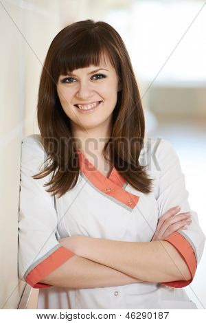 Portrait of smiling young nurse doctor in medic uniform in hospital clinic hall
