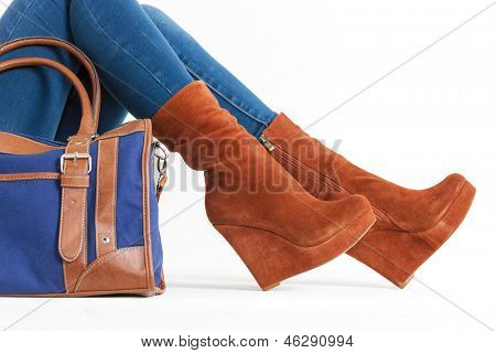 detail of sitting woman wearing fashionable platform brown shoes with a handbag