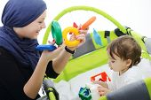 stock photo of hijab  - Arabic Muslim mother playing and taking care of her baby - JPG
