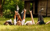 stock photo of singing  - Four happy friends relax with guitar music on the green medow - JPG