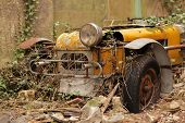 picture of junk-yard  - Old forgotten car rusting at the backyard of an old english property - JPG