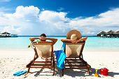 stock photo of beach hat  - Couple on a tropical beach at Maldives - JPG