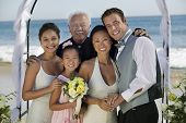 Portrait of a bride and groom with family at the beach wedding