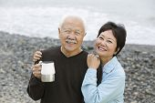stock photo of japanese woman  - Portrait of a happy and loving mature couple at the beach - JPG