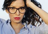 Beautiful young woman wearing eye glasses and blue dress shirt