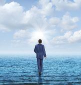 stock photo of impossible  - Walk on water with a businessman walking on the surface of an ocean as a business concept of confidence and courage to take on an impossible challenge and achieve success with the power of belief - JPG