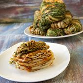 stock photo of kimchi  - A plate of sliced and stacked kimchi and a plate of wrapped and uncut kimchi - JPG