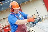 image of millwright  - Builder worker with power tool circular saw machine cutting plastic parts at construction site - JPG