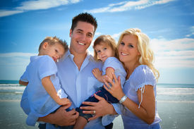 picture of family vacations  - Family on a beach standing looking into camera - JPG