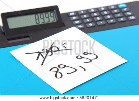 Piece of paper showing the amount of 89,99 lying on a calculator showing the same number.