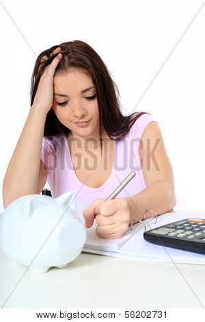 Attractive teenage girl in desperate mood while doing her budget. All on white background.