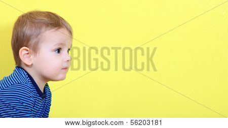 Cute caucasian toddler looking to the right. Extra text space on right side.