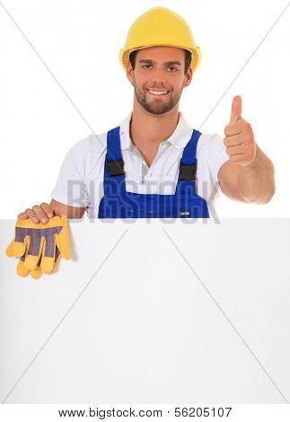 Construction worker making thumbs up while standing behind white wall. All on white background.