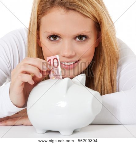Attractive teenage girl puts 10 euro into piggy bank. All on white background.