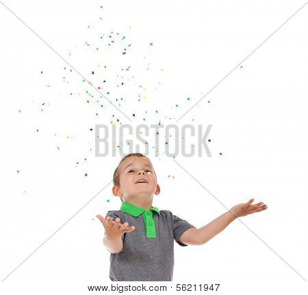 Attractive young boy playing with confetti. All on white background.