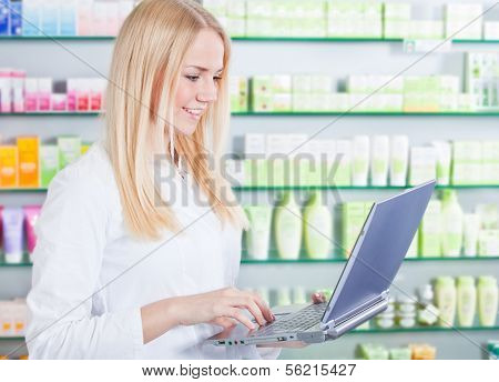 Attractive saleswoman in pharmacy using laptop.