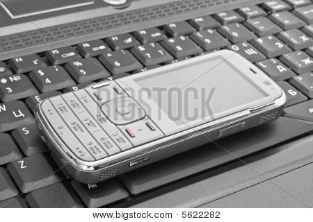 Mobile Phone Lies On The Laptop Keyboard