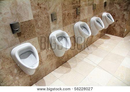row of urinals in empty clean restroom