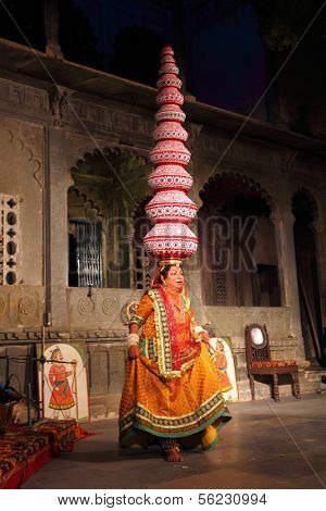 UDAIPUR, INDIA - NOVEMBER 24: Bhavai performance - famous folk dance of Rajasthan state. Performer balances number of pots as she dances on broken glass. November 24, 2012 in Udaipur, Rajasthan, India