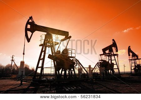 working oil pumps silhouette against sun