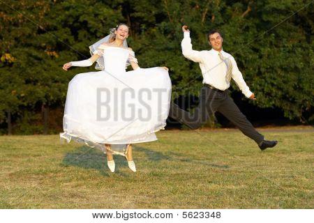 glückliche Brautpaar-springen