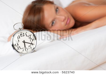 Alarm Clock Standing On Bed, Woman In Background