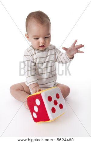 Baby boy plays with a soft dice toy on white background