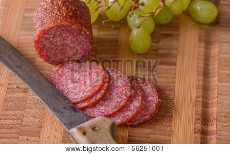 Closeup Of Salami With A Knife And Some Grapes On The Side
